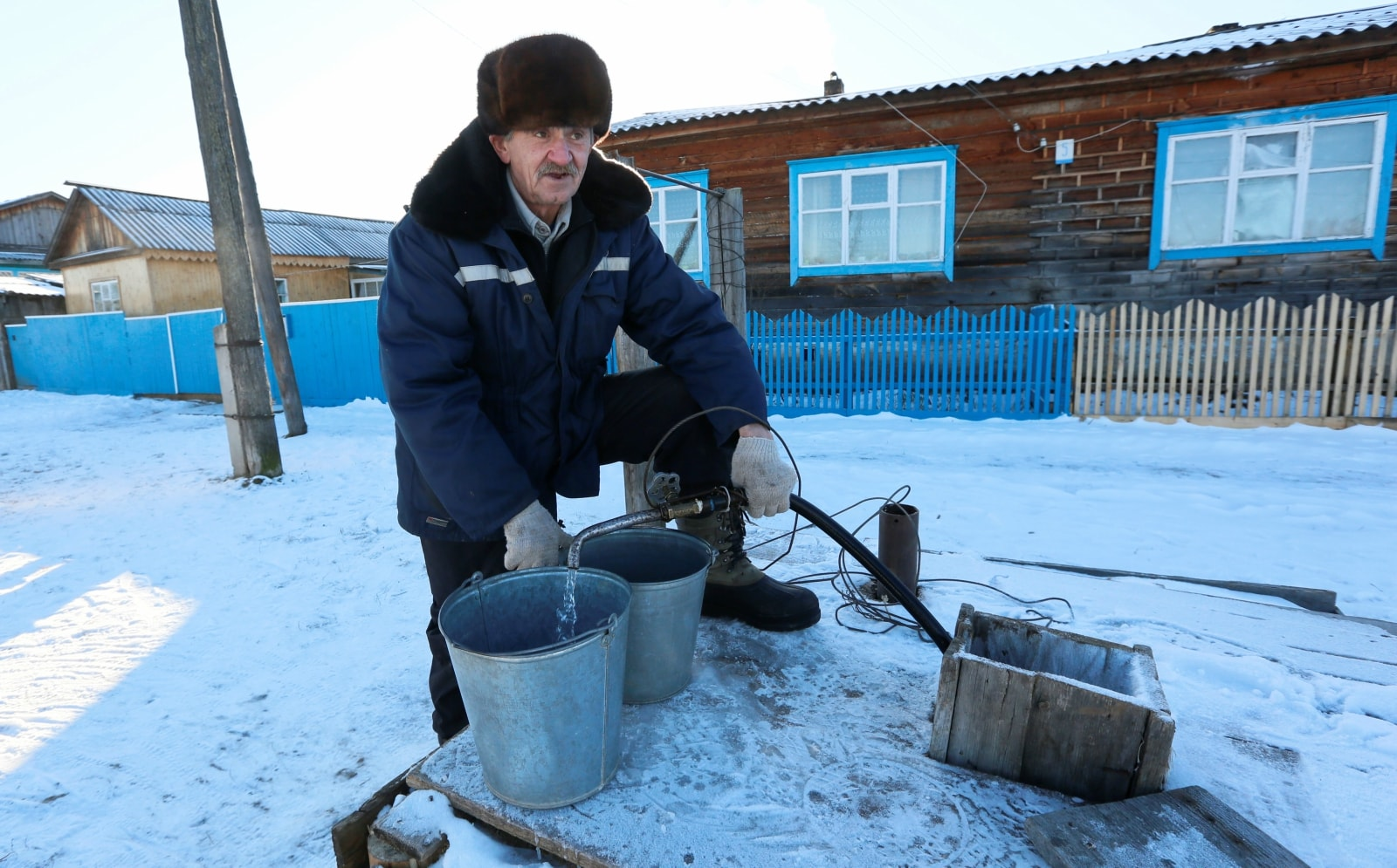 Local resident Alexander Lazarev, 69, pumps water from a street well in a Siberian settlement, which was founded as a logging camp and part of the Soviet Union's Gulag prison labour system, Tugach, southeast of Krasnoyarsk, Russia November 18, 2018. REUTERS/Ilya Naymushin