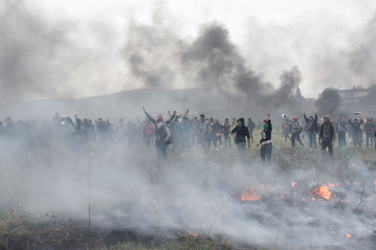 Migrants and refugees are seen among smoke during clashes outside a camp in the town of Diavata in northern Greece. (REUTERS/Alexandros Avramidis)