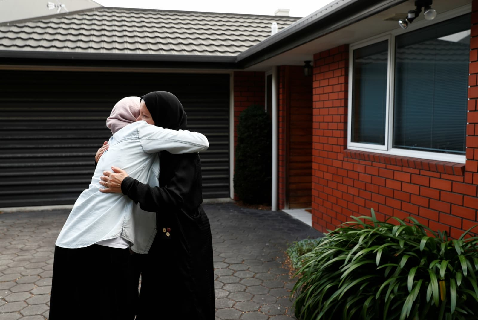 Zahra Fathy, the widow of 70-year-old Hussein Moustafa, an Egyptian immigrant who lost his life in the Christchurch shootings, embraces a neighbour who came to check on how Zahra was coping, outside her house in Christchurch, New Zealand March 30, 2019. REUTERS/Edgar Su