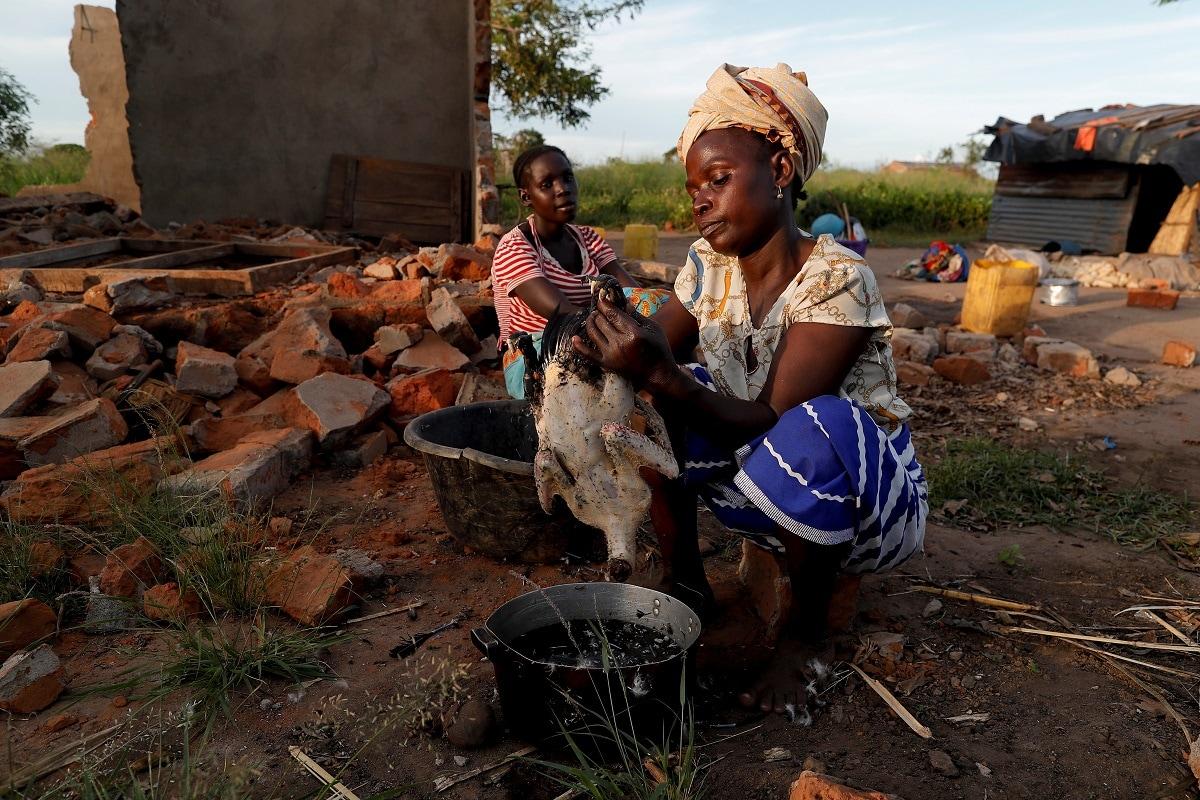 Maria Jofresse watches her mother Ester Thoma preparing food beside their damaged house. (REUTERS/Zohra Bensemra)