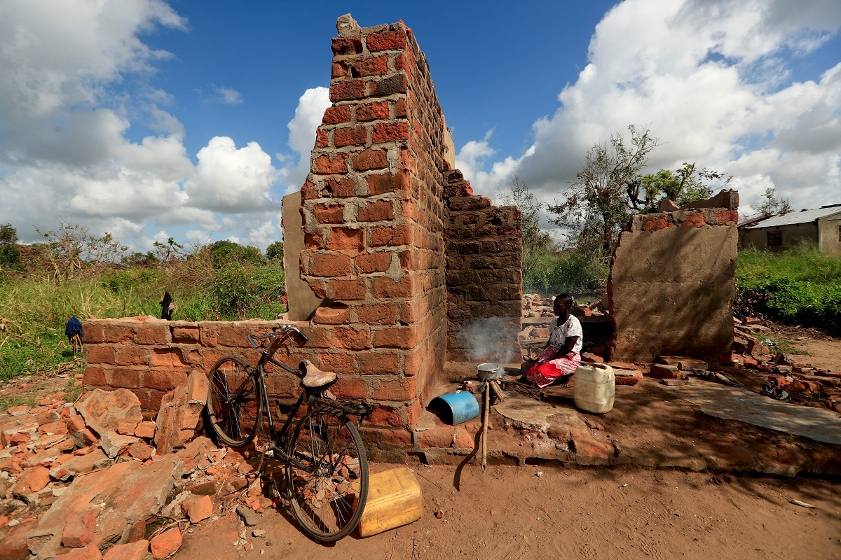 Ester Thoma cooks at her damaged house in the aftermath of Cyclone Idai. (REUTERS/Zohra Bensemra)