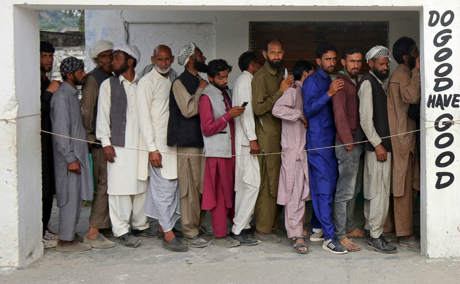 People wait in a queue to cast their votes outside a polling station during the first phase of general election on the outskirts of Jammu April 11, 2019. REUTERS/Mukesh Gupta