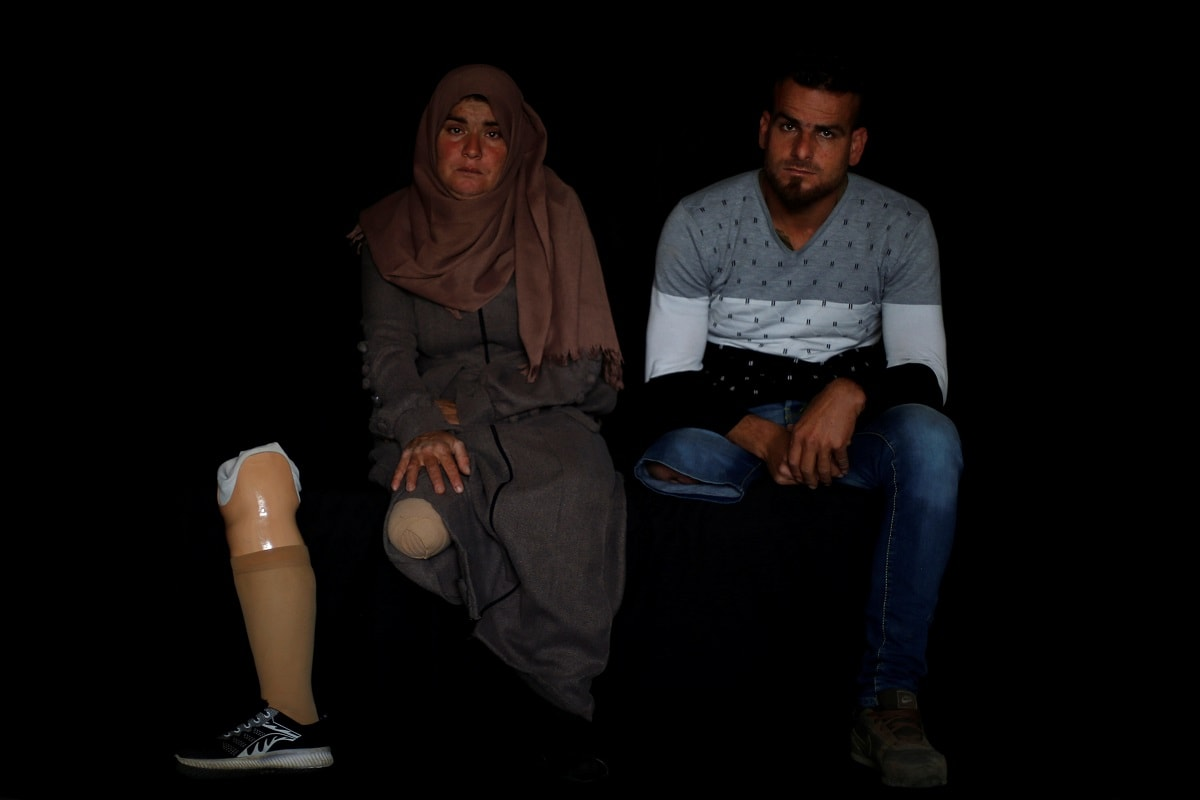 Palestinian woman Nazeeha Qudieh, 38, and her brother Suhaib, 33, who, according to medics, both lost a leg after they were shot by Israeli forces during a protest at the Israel-Gaza border, pose for a photo inside their home in Khan Younis in the southern Gaza Strip. (REUTERS/Mohammed Salem/Files)