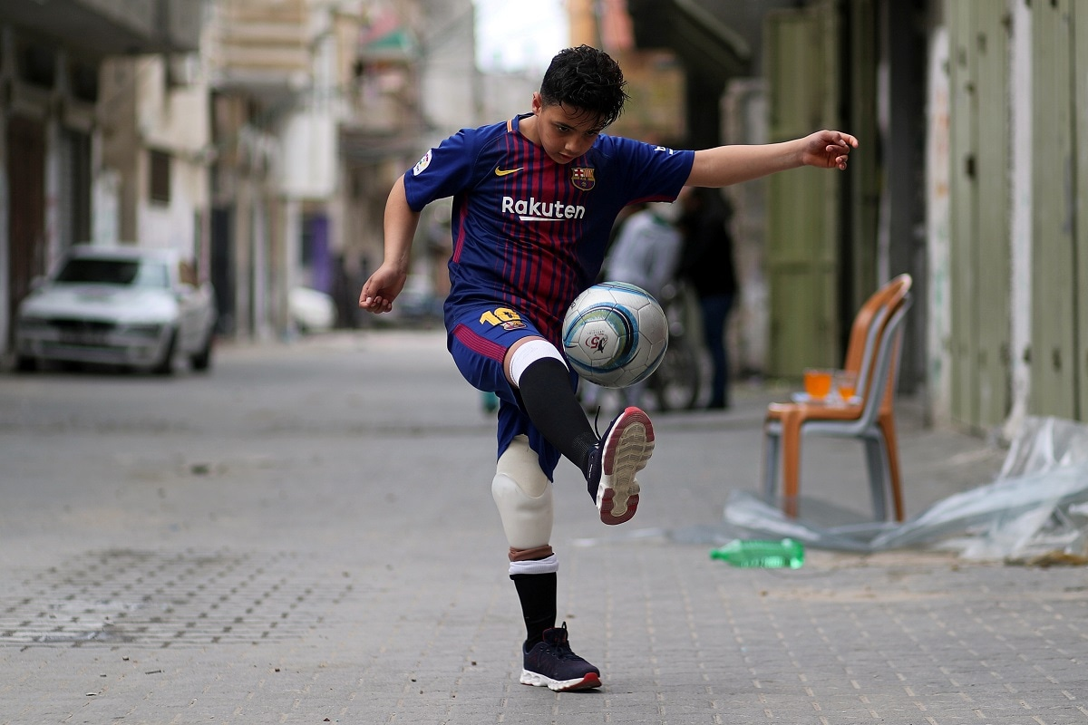 Palestinian boy Abdel-Rahman Nofal, 12, who, according to medics, lost his left leg after he was shot by Israeli forces during a protest at the Israel-Gaza border, plays soccer outside his house in the central Gaza Strip. (REUTERS/Mohammed Salem/Files)
