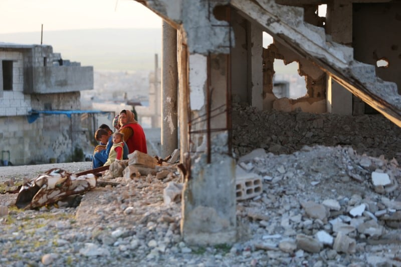 A woman sits with children on a rubble from damaged buildings in Kobani, Syria April 3, 2019. Picture taken April 3, 2019. REUTERS/Ali Hashisho