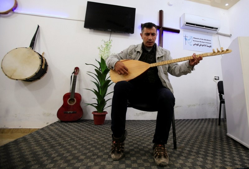 Omar Firas, the founder of KobaniÕs evangelic church plays on an string instrument inside a church in Kobani, Syria April 3, 2019. Picture taken April 3, 2019. REUTERS/Ali Hashisho