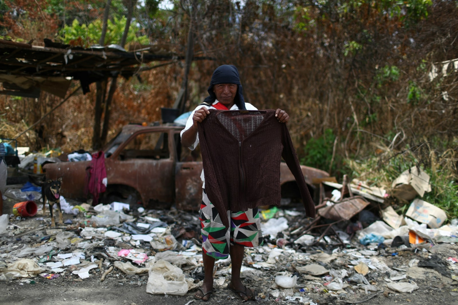 Venezuelan Euclide Mata holds a sweater after scraping on a garbage dump in the border city of Pacaraima, Brazil April 15, 2019. REUTERS/Pilar Olivares