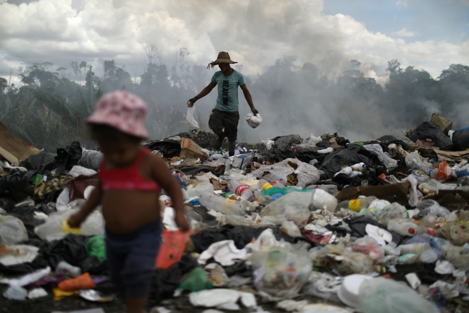 Venezuelan Antony Calzadilla is seen at a garbage dump as his child waits for him, in the border city of Pacaraima, Brazil April 13, 2019. REUTERS/Pilar Olivares