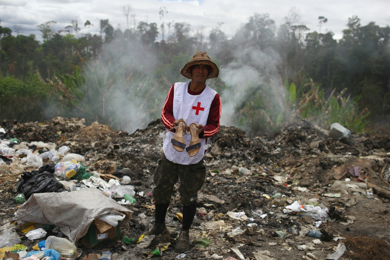 Venezuelan Charles Sanchez holds a pair of shoes after scraping on a garbage dump in the border city of Pacaraima, Brazil April 15, 2019. REUTERS/Pilar Olivares