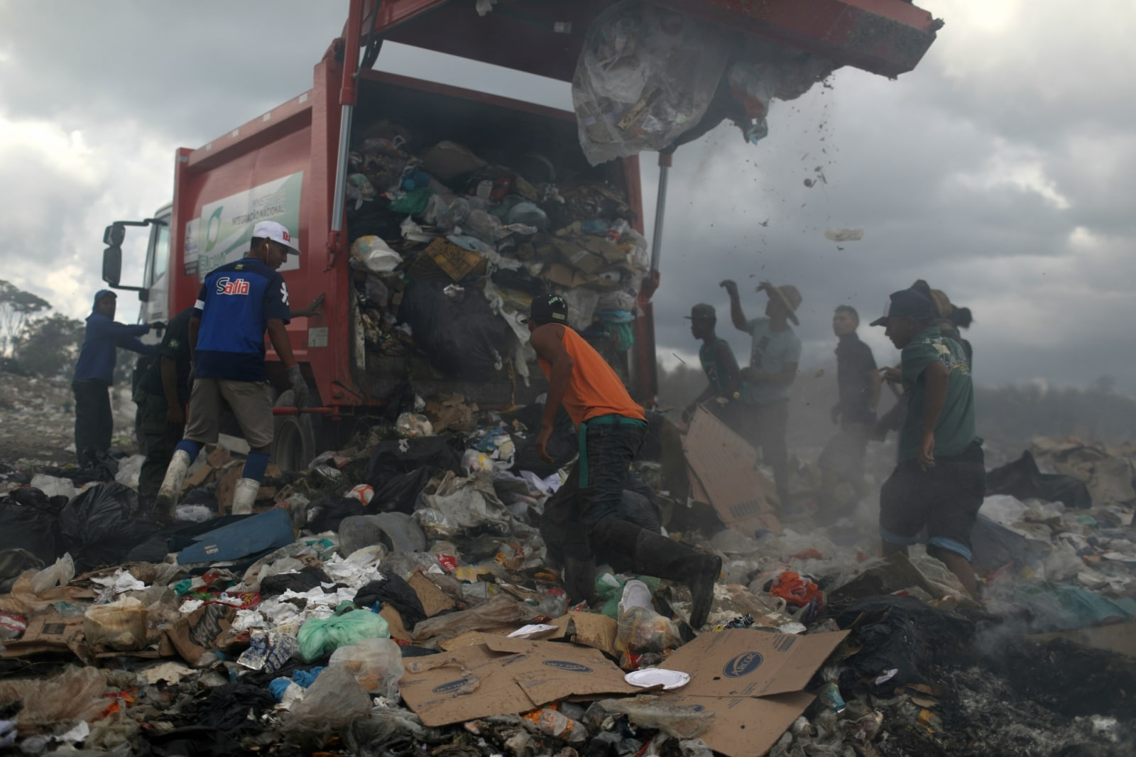 Venezuelan migrants wait while the rubbish truck unloads at the garbage dump in the border city of Pacaraima, Brazil April 13, 2019. REUTERS/Pilar Olivares