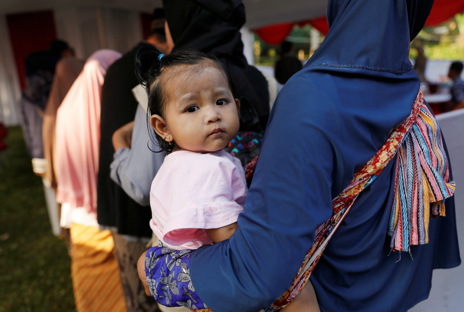 A woman carrying her child queues up at a polling booth to vote during elections in Bogor, West Java, Indonesia April 17, 2019. REUTERS/Willy Kurniawan