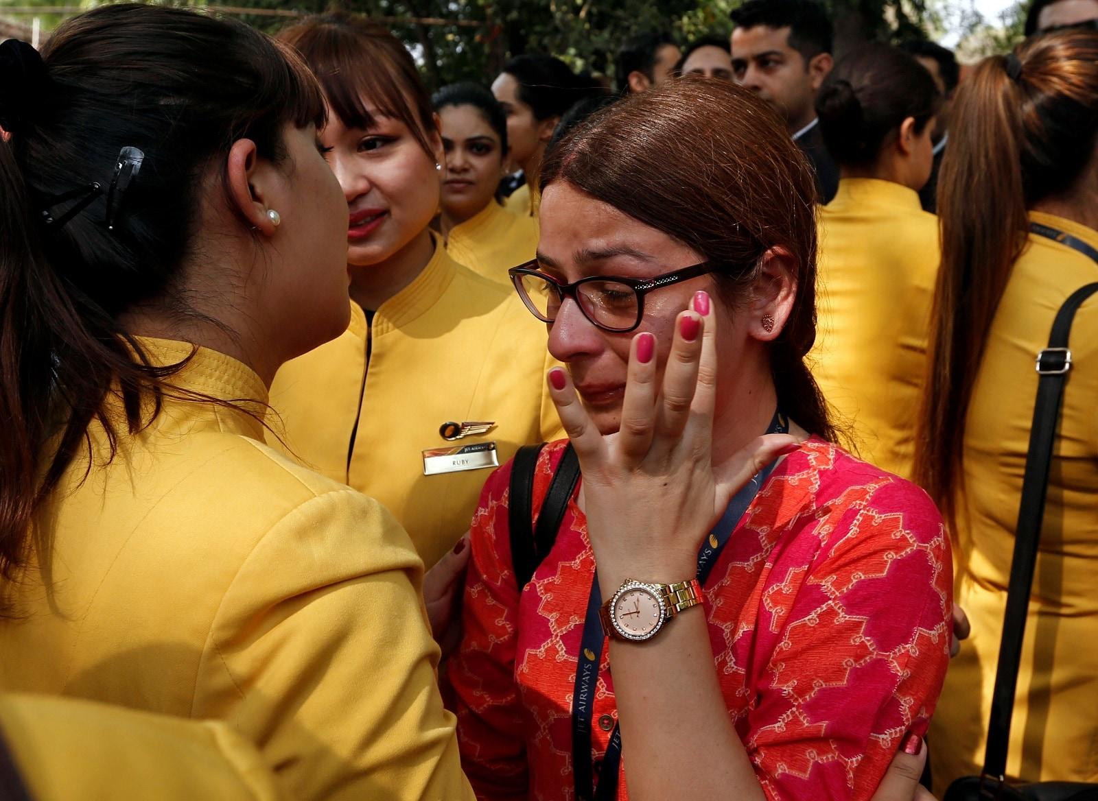 An employee of Jet Airways is consoled by her colleagues during a protest demanding to