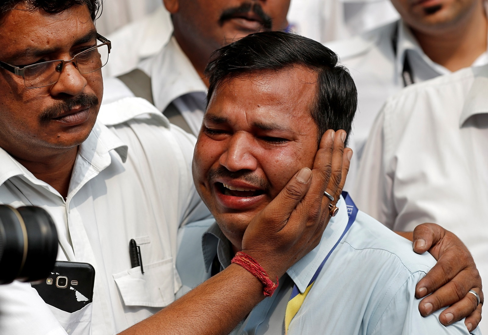 An employee of Jet Airways is consoled by his colleague during a protest demanding to
