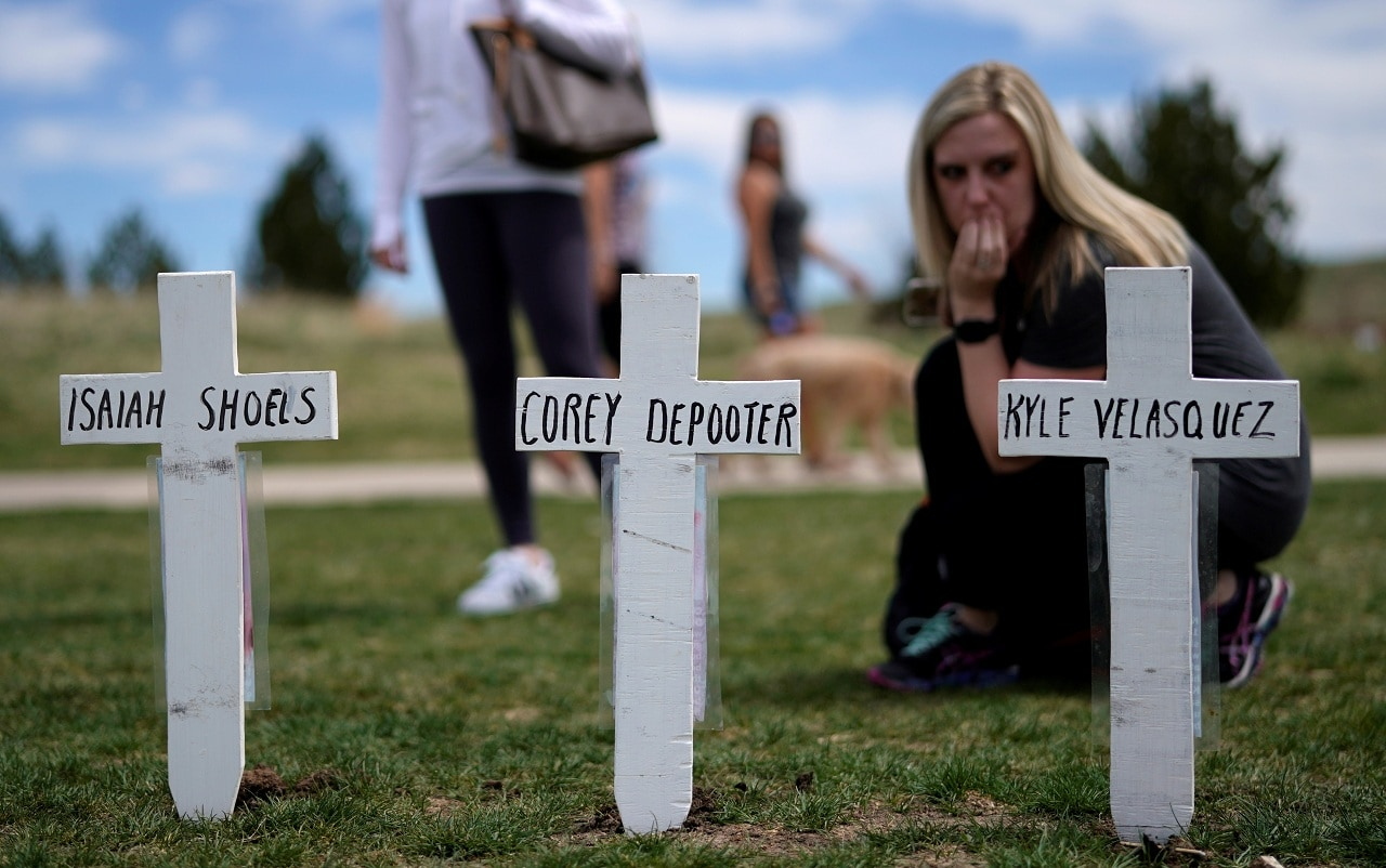 Cassanda Sadusky, survivor of the attack, looks at a line of crosses commemorating those killed in the Columbine High School shooting on the 20th anniversary of the attack in Littleton, Colorado, U.S., April 20, 2019. REUTERS/Rick Wilking