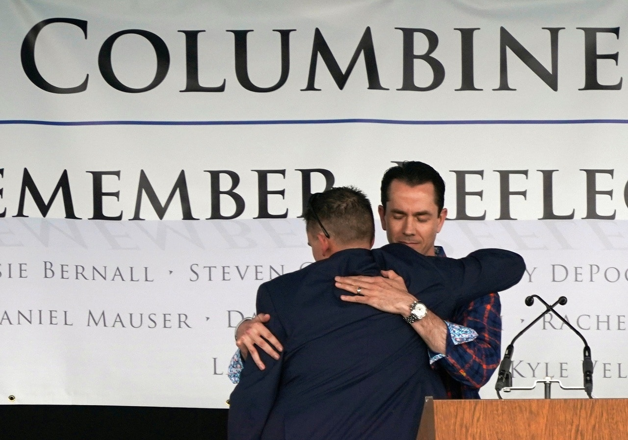 Sean Graves, shot six times in the Columbine high school shooting (L), hugs Patrick Ireland, shot in the head in the shooting, at a ceremony to commemorate the 20th anniversary of the attack in Littleton, Colorado, U.S., April 20, 2019. Graves was paralyzed from the neck down but after dozens of surgeries can now walk. REUTERS/Rick Wilking