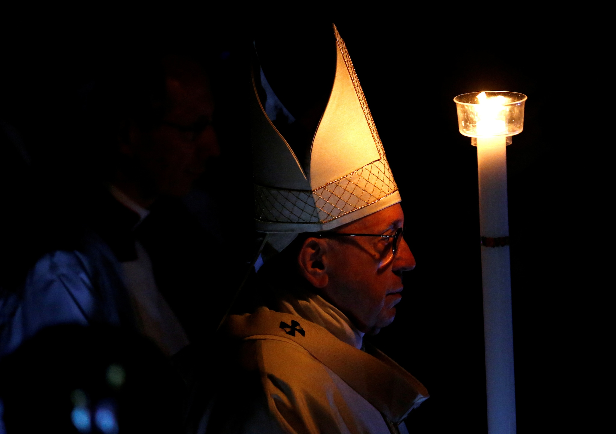 Pope Francis holds a candle as he leads the Easter vigil mass in Saint Peter's Basilica at the Vatican, March 31, 2018. REUTERS/Stefano Rellandini