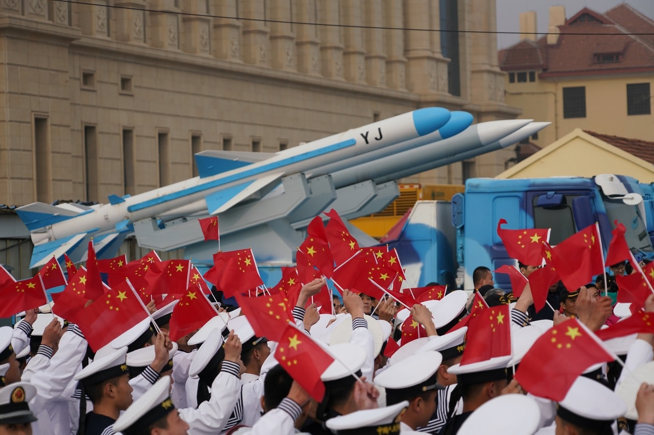Chinese People's Liberation Army (PLA) Navy soldiers wave Chinese flags next to a model of a military vehicle carrying anti-ship missiles, during an event marking the 70th anniversary of the founding of Chinese People's Liberation Army Navy on April 23, at the navy museum in Qingdao, Shandong province, China April 13, 2019. Picture taken April 13, 2019. REUTERS/Stringer