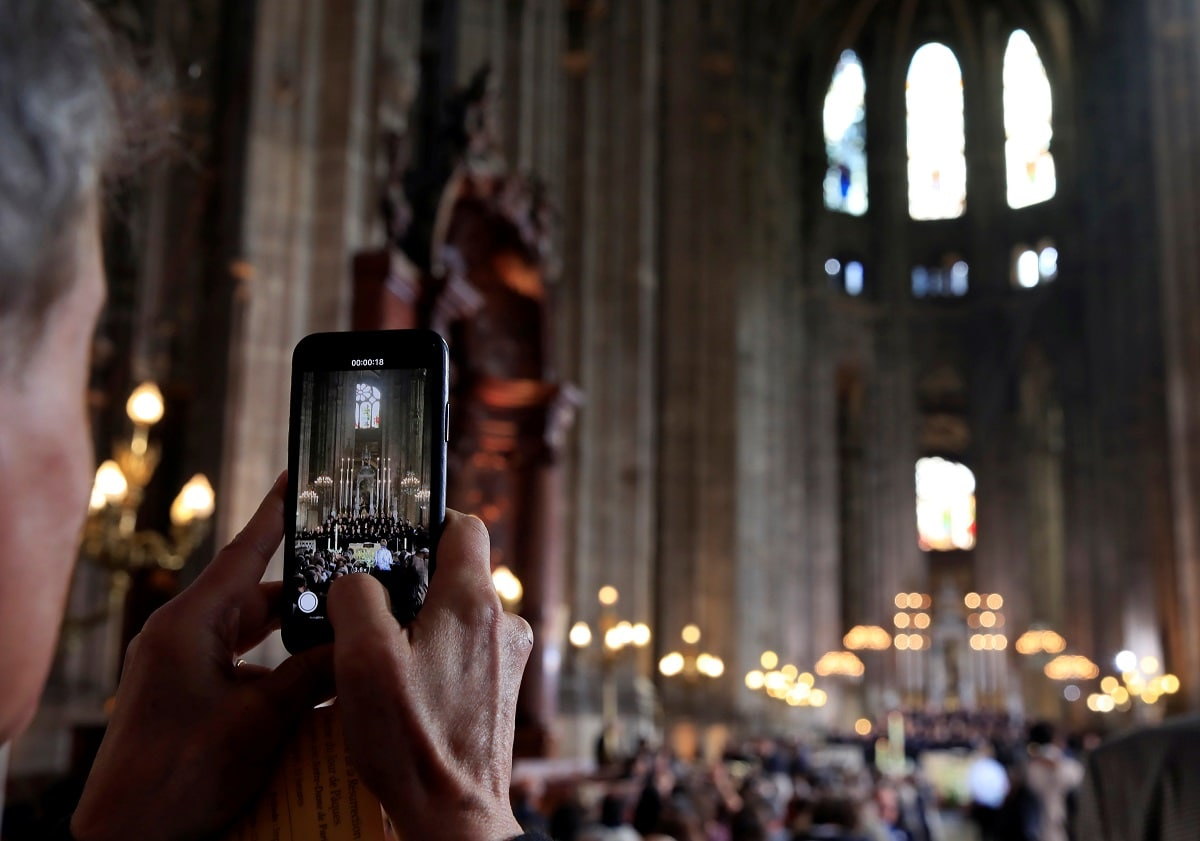 A man takes a photo before Easter Sunday Mass at Saint-Eustache, days after a massive fire devastated large parts of the structure of the gothic Notre-Dame Cathedral. REUTERS/Gonzalo Fuentes