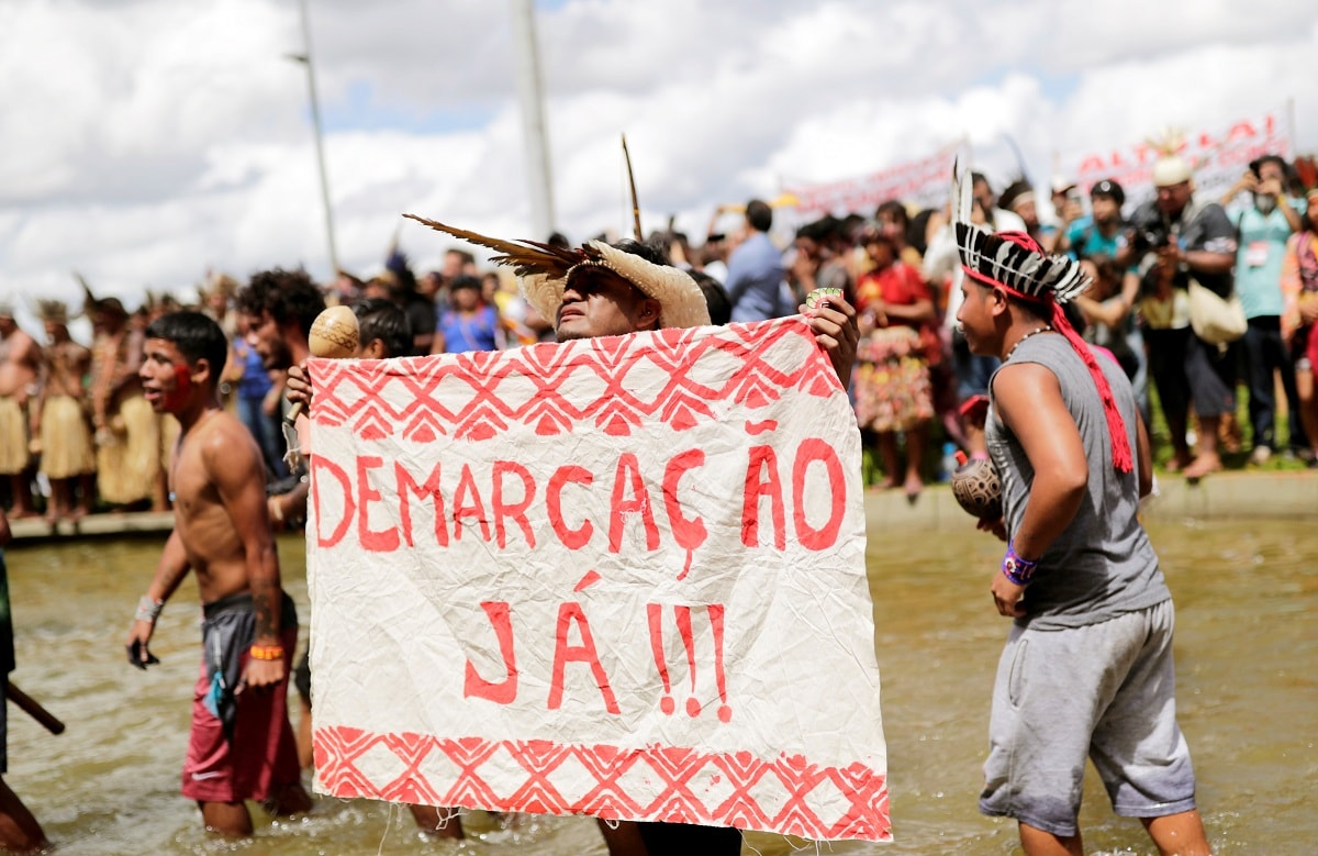 An indigenous man holds a sign reading