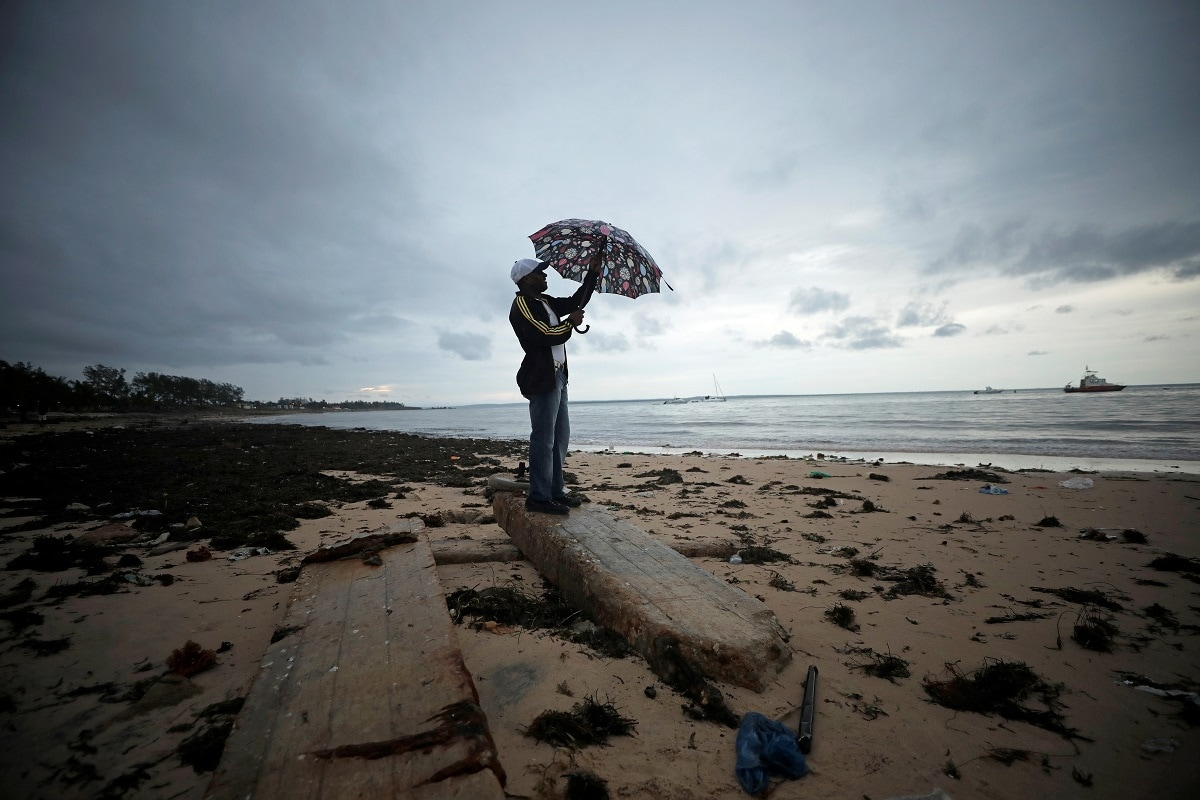 A man holds an umbrella beneath storm clouds over Wimbe beach, as the region braces for further rainfall in the aftermath of Cyclone Kenneth in Pemba Mozambique. (REUTERS/Mike Hutchings)