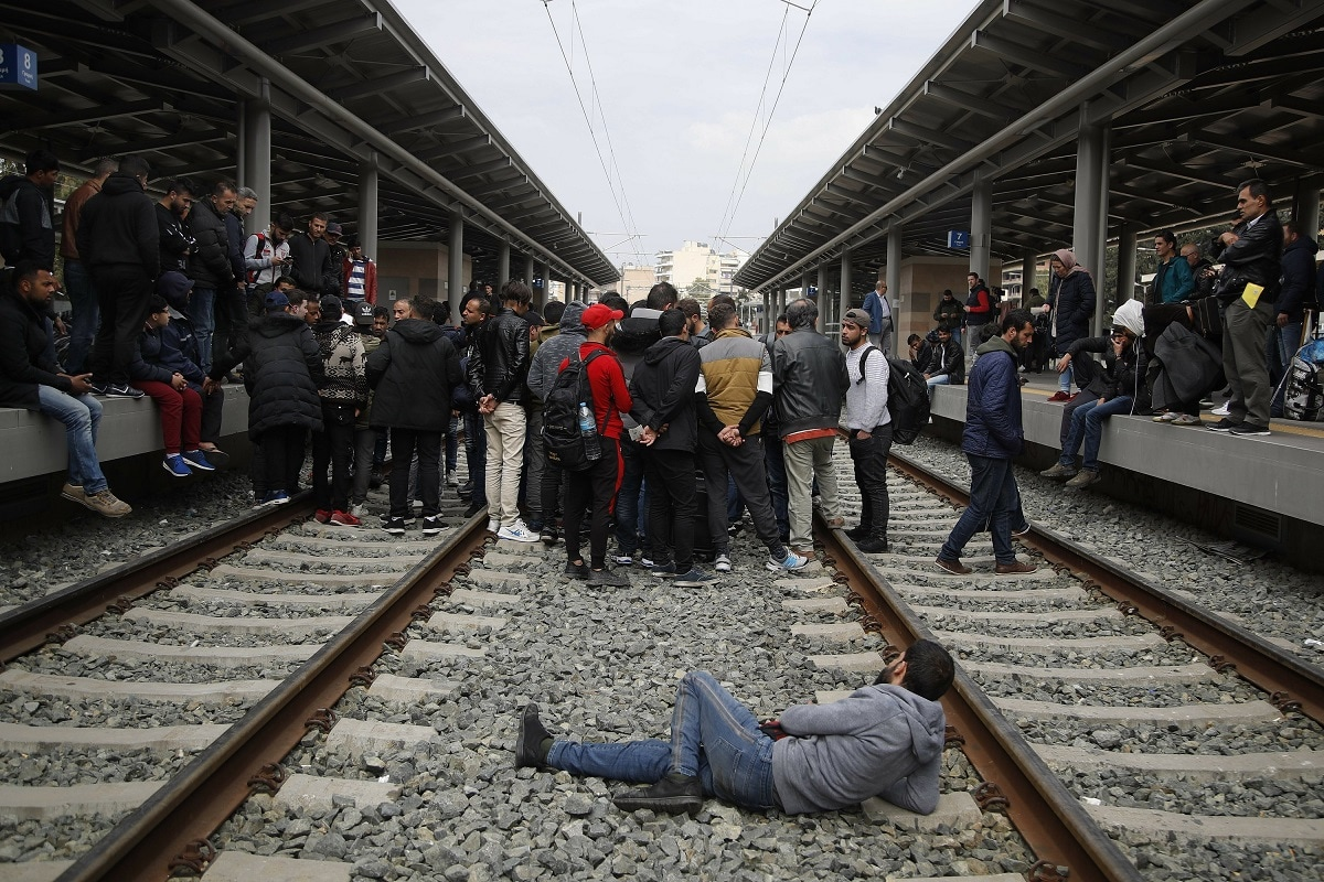 Migrants stand on the railway as they blocked the Larissis main rail station in Athens. (AP Photo/Thanassis Stavrakis)