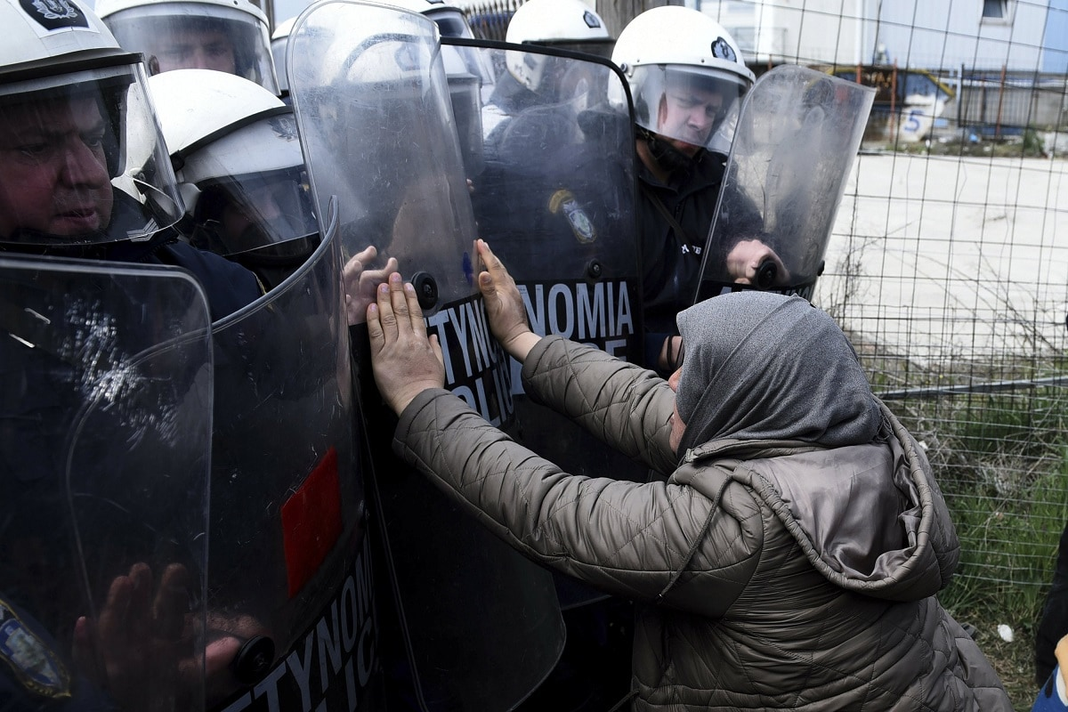A migrant woman pushing with riot police outside a refugee camp in the village of Diavata. (AP Photo/Giannis Papanikos)