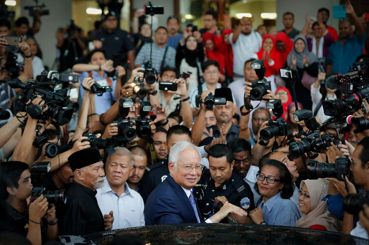 Former Prime Minister Najib Razak, center, gets into a car after his court appearance at the Kuala Lumpur High Court in Kuala Lumpur, Malaysia. Najib appeared in court Wednesday for the start of his corruption trial, exactly 10 years after he was first elected to office only to suffer a spectacular defeat last year on allegations he pilfered millions of dollars from a state investment fund. (AP Photo/Vincent Thian, File)