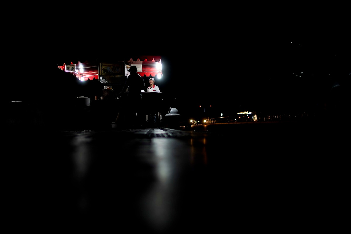 Food vendors wait for customers on a darkened street in Caracas. Many street lights don't work after a string of devastating nationwide blackouts last month. (AP Photo/Natacha Pisarenko)