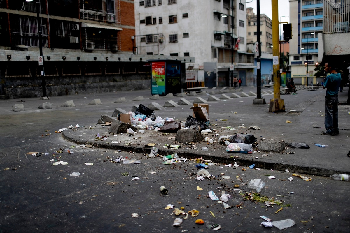 Garbage lays scattered on the pavement in Caracas. The poor and hungry scour through household trash, scattering it across street corners before it's collected, grabbing anything they can use or eat. (AP Photo/Natacha Pisarenko)