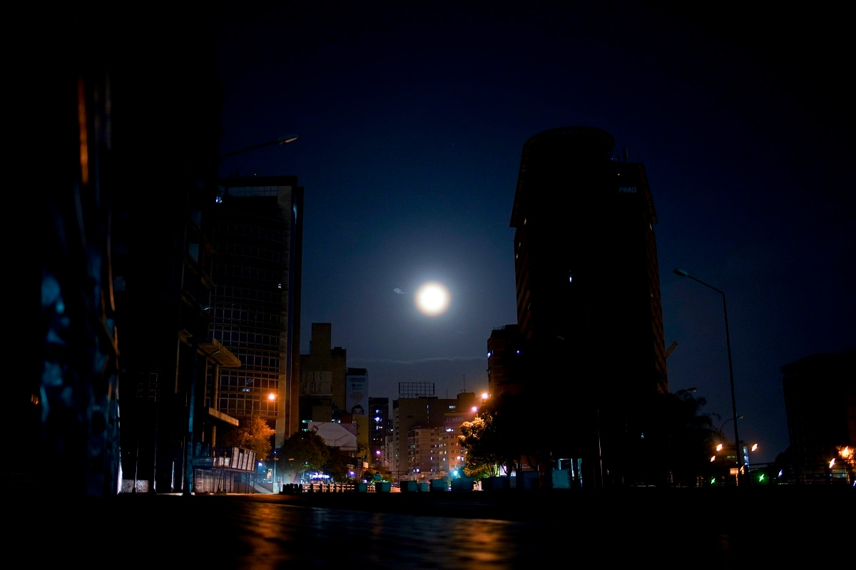 The moon rises above an empty avenue in Caracas. Residents avoid stepping outside their homes due to crime, or for lack of anything to spend. (AP Photo/Natacha Pisarenko)