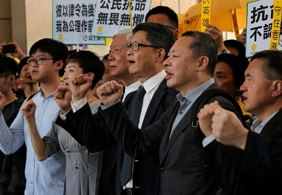 Occupy Central leaders, from right, Benny Tai, Chan Kin-man, Chu Yiu-ming, Tanya Chan and Eason Chung shout slogans before entering a court in Hong Kong. Nine leaders of the 2014 Hong Kong pro-democracy movement arrived at the court to hear the verdicts in their trial. The co-founders of the