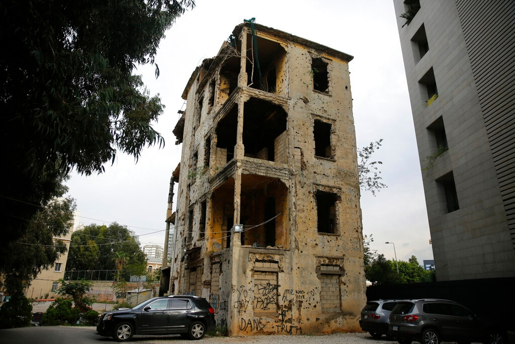 In this December 2, 2018, photo, cars park in front of a building that is still riddled with bullets and shells on the former frontline of the 1975-1990 Lebanese civil war in Beirut, Lebanon. (AP Photo/Hassan Ammar)