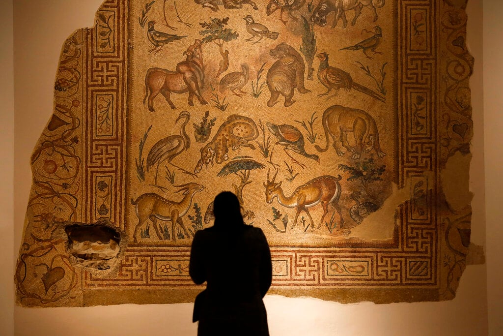 In this January 28, 2016, photo, a visitor checks the mosaic of the Good Shepherd that was badly damaged in the lower left corner by a sniper during the 1975-1990 Lebanese civil war at the Lebanese National Museum in Beirut, Lebanon. (AP Photo/Hassan Ammar)