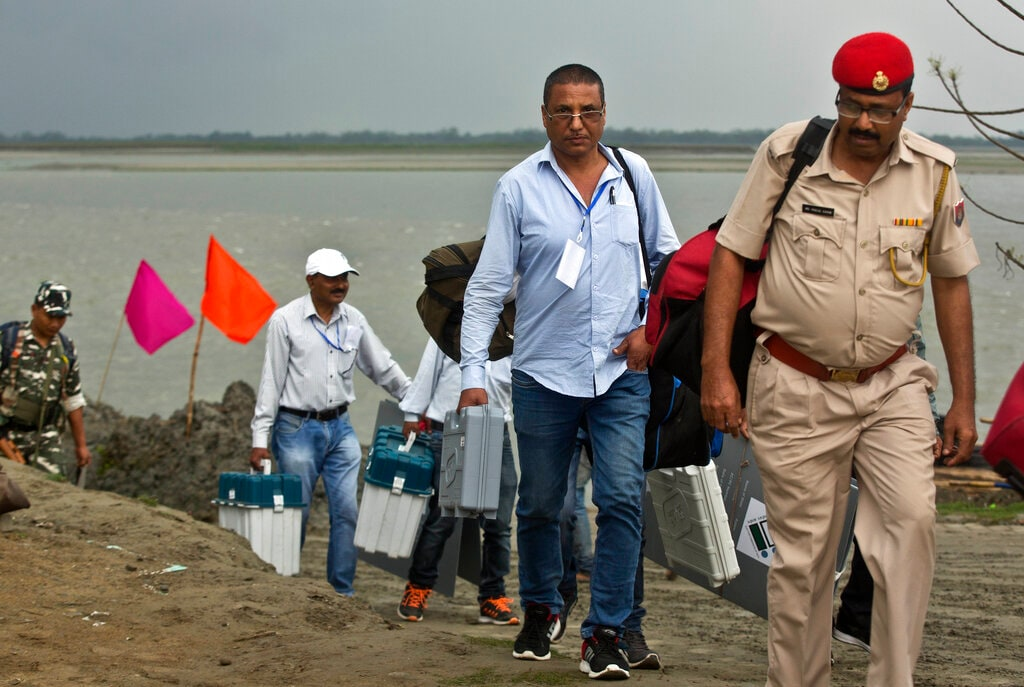 Indian election officials carry election material after disembarking from a ferry through the river Brahmaputra ahead of the first phase of elections at Nimati Ghat in Jorhat, Assam, India, Tuesday, April 9, 2019. India's general elections will be held in seven phases starting April 11. (AP Photo/Anupam Nath)