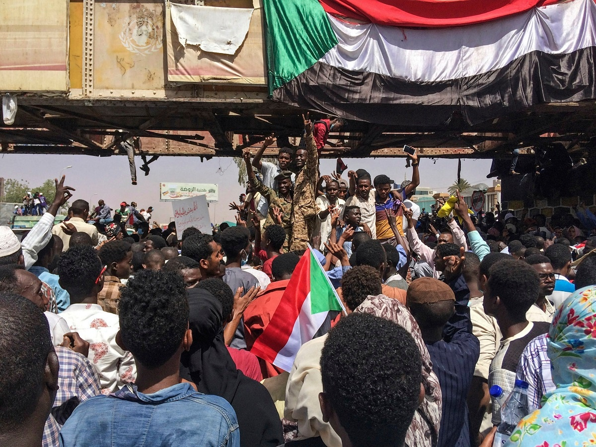 Uniformed Sudanese soldiers flash the victory sign as they stand among protesters at a demonstration. (AP Photo)