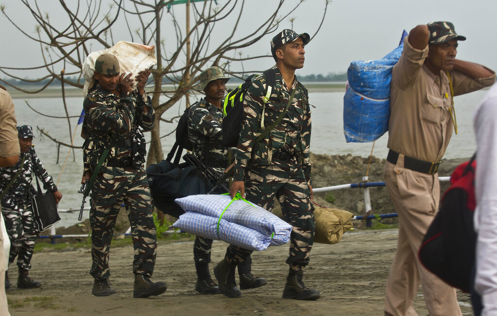 Indian paramilitary soldiers carry their luggage after disembarking from a ferry through the river Brahmaputra ahead of the first phase of elections at Nimati Ghat in Jorhat, Assam, India, Tuesday, April 9, 2019. India's general elections will be held in seven phases starting April 11. (AP Photo/Anupam Nath)