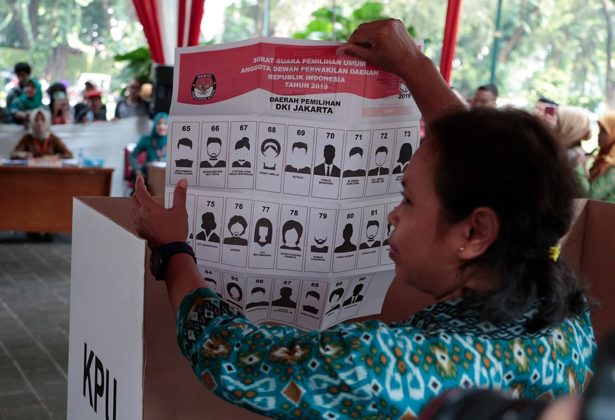 A woman shows a mock ballot for the senate during a polling simulation exercise held by the election commission in Jakarta, Indonesia. (AP Photo/Dita Alangkara, File)