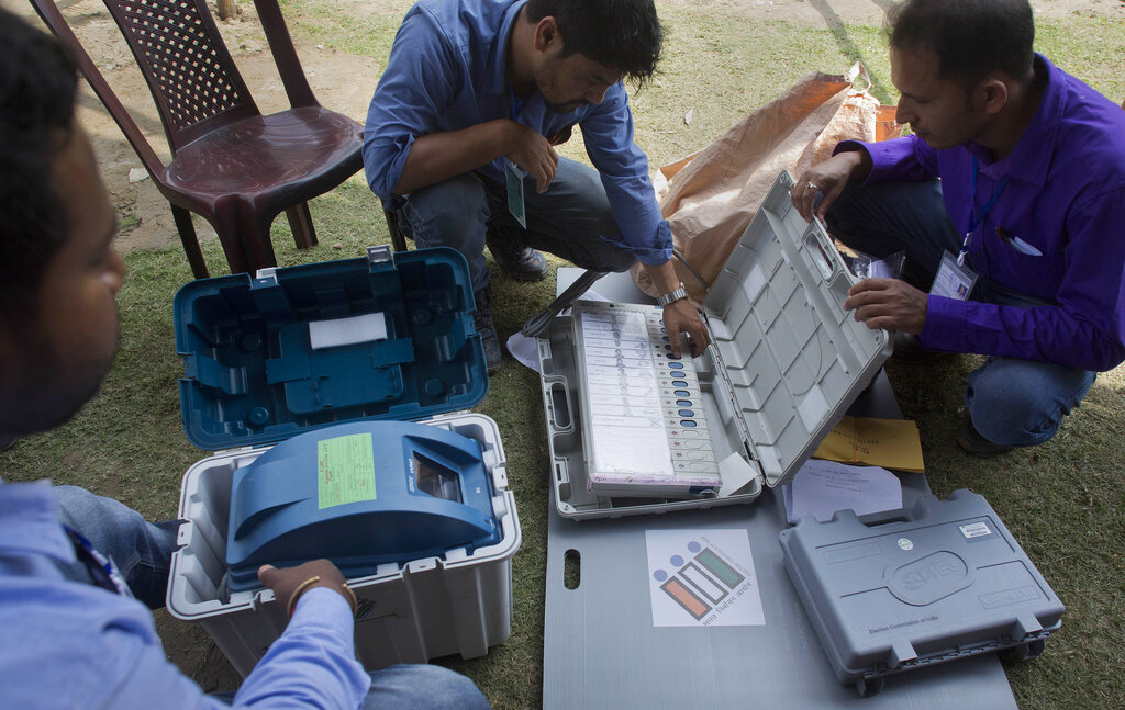 In this April 10, 2019, photo, polling officials check their electronic voting machines and voter-verifiable paper audit trail (VVPAT) before being deployed to a polling station on the eve of the first phase of the general election in Majuli, Assam, India. (AP Photo/Anupam Nath)