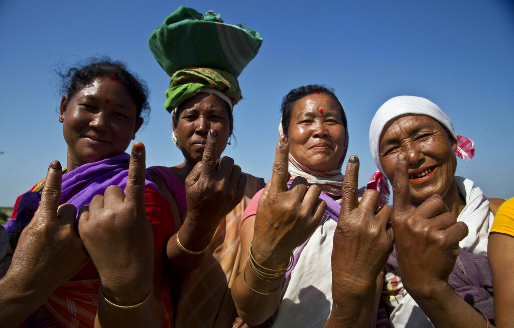 In this April 11, 2019, photo, Mishing tribal women show the indelible ink marks on their index fingers after casting their votes in Majuli, Assam, India. (AP Photo/Anupam Nath)