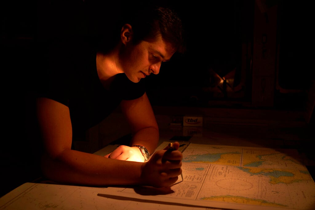 Second officer Konstantin Afanasjev studies the chart of St. Joseph Island in Seychelles during his night watch on board the Ocean Zephyr, Thursday, April 11, 2019. The Ocean Zephyr is the mothership of the British-based Nekton Mission which is exploring the Indian Ocean. Scientists hope to document changes taking place beneath the waves that could affect billions of people in the surrounding region over the coming decades. (AP Photo/David Keyton)