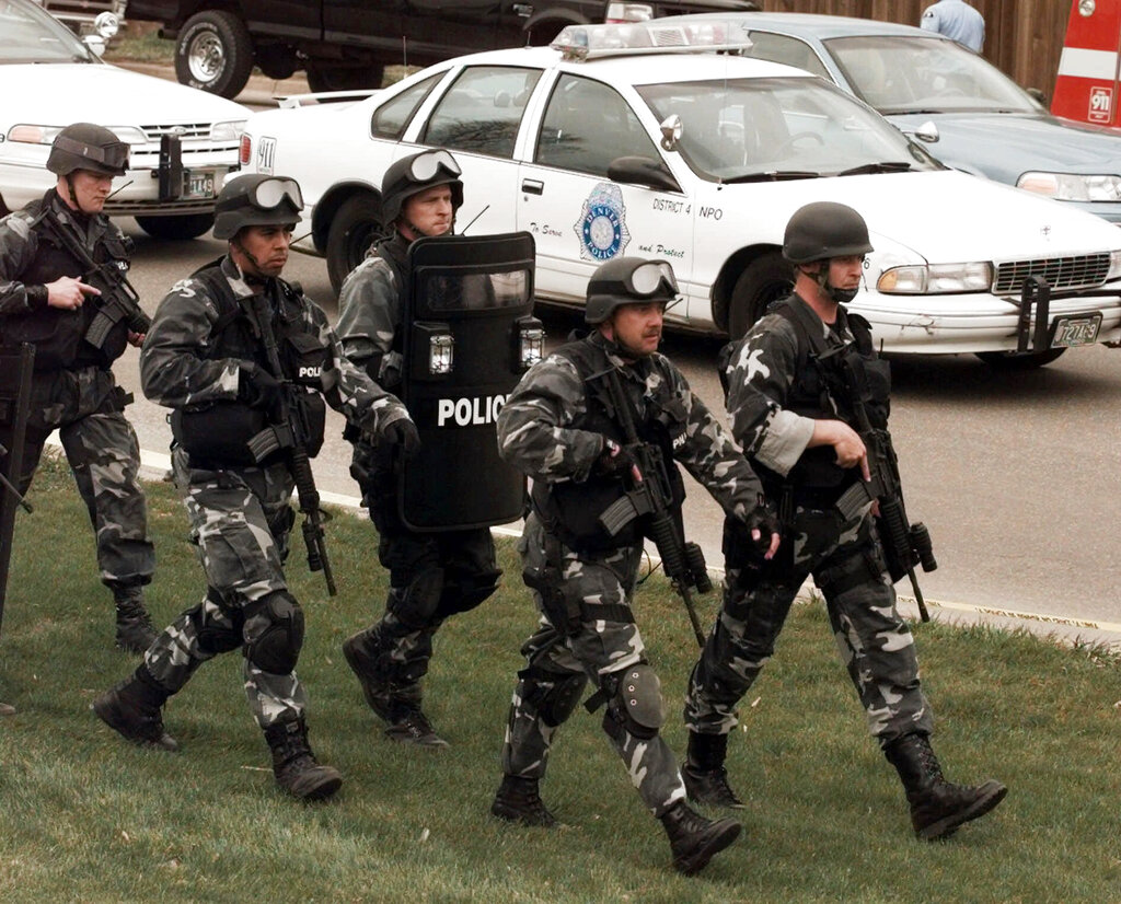 In this April 20, 1999, file photo, members of a police SWAT team march to Columbine High School in Littleton, Colo., as they prepare to do a final search of the school after two gunmen opened fire on campus. The shooting shocked the country as it played out on TV news shows from coast to coast. (AP Photo/Ed Andrieski, File)