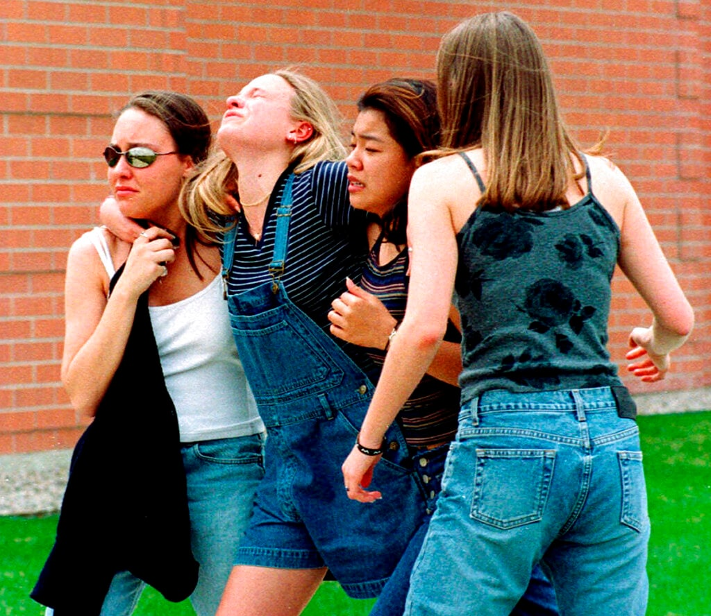 In this April 20, 1999, file photo, women head to a library near Columbine High School where students and faculty members were evacuated after two gunmen went on a shooting rampage in the school in the Denver suburb of Littleton, Colo. Twelve students and one teacher were killed in a murderous rampage at the school on April 20, 1999, by two students who killed themselves in the aftermath. (AP Photo/Kevin Higley, File)