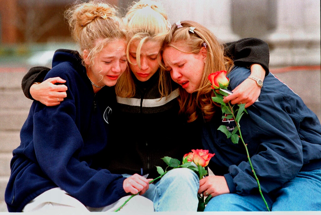 In this April 21, 1999, file photo, from left, Rachel Ruth, Rhianna Cheek and Mandi Annibel, all 16-year-old sophomores at Heritage High School in Littleton, Colo., console each other during a vigil service to honor the victims of the shooting spree in Columbine High School in the southwest Denver suburb of Littleton, Colo. (AP Photo/Laura Rauch, File)