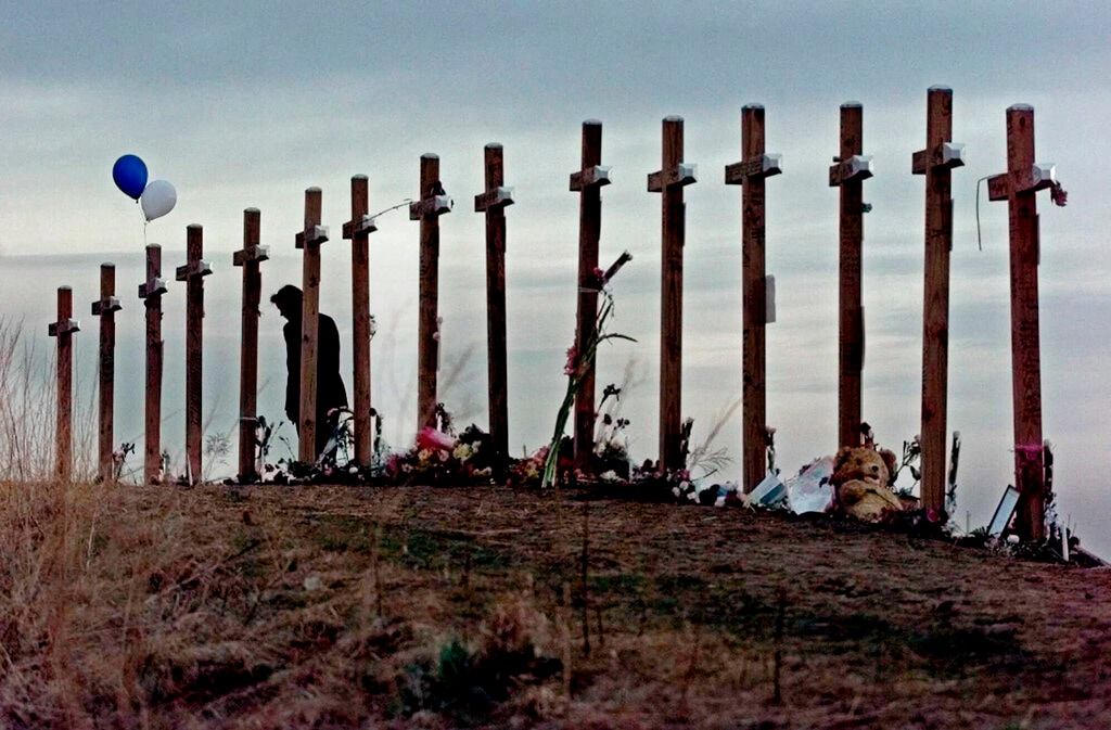 In this April 28, 1999, file photo, a woman looks at crosses posted on a hill above Columbine High School in Littleton, Colo., in remembrance of the people who died during a shooting rampage at the school. (AP Photo/Eric Gay, File)