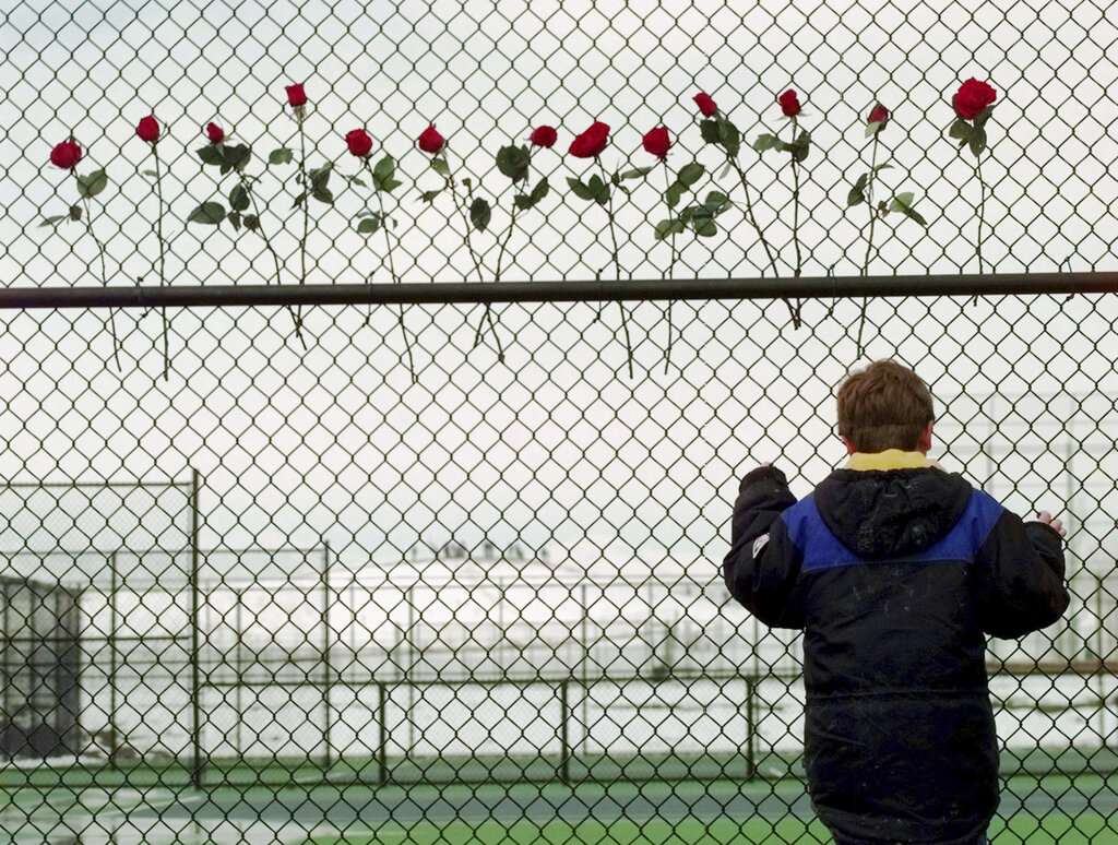 In this April 24, 1999, file photo, a boy looks through the fence at the Columbine High School tennis courts in Littleton, Colo. Thirteen roses were placed on the fence in remembrance of the 13 people killed by two gun-wielding students at the school. (AP Photo/Eric Gay, File)