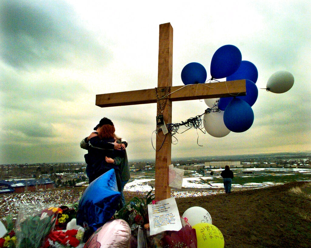In this April 24, 1999, file photo, students embrace each other at a makeshift memorial for their slain classmates at Columbine High School on a hilltop overlooking the school in Littleton, Colo. (AP Photo/Bebeto Matthews, File)