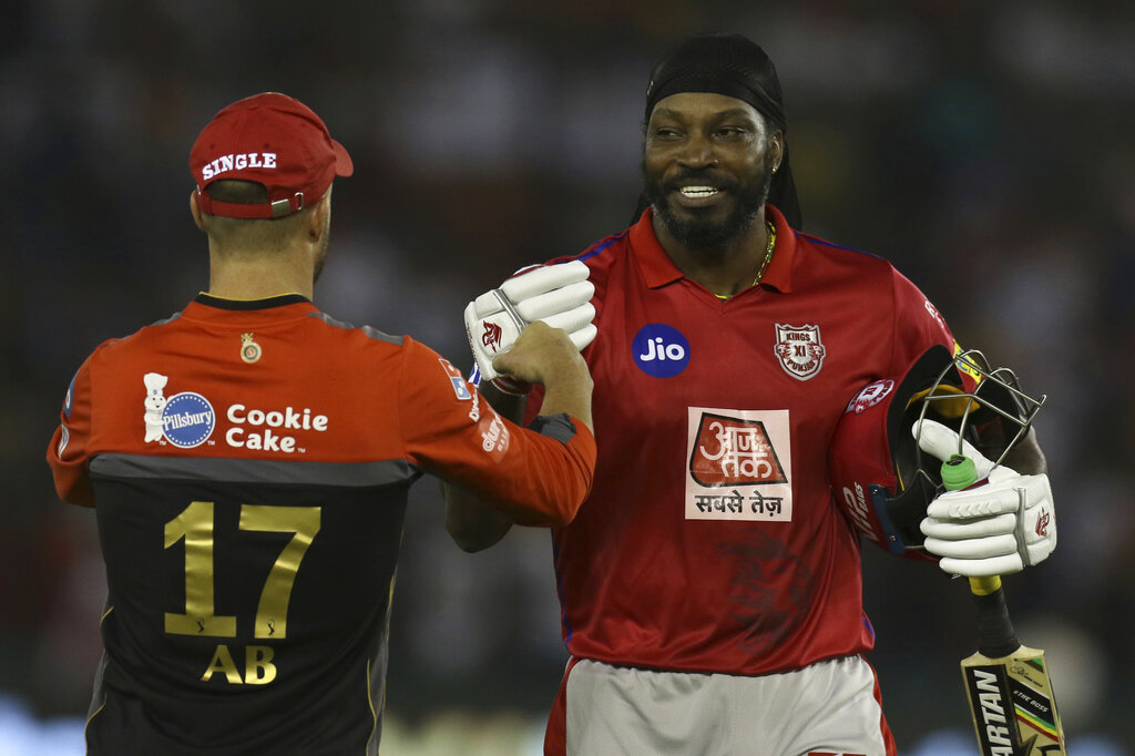 Chris Gayle of Kings XI Punjab, right, greets AB de Villiers during the VIVO IPL T20 cricket match between Kings XI Punjab and Royal Challengers Bangalore in Mohali, India, Saturday, April 13, 2019. (AP Photo/Surjeet Yadav)