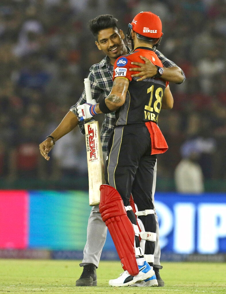A fan runs hugs Virat Kohli, captain of Royal Challengers Bangalore, after running into the field during the VIVO IPL T20 cricket match between Kings XI Punjab and Royal Challengers Bangalore in Mohali, India, Saturday, April 13, 2019. (AP Photo/Surjeet Yadav)