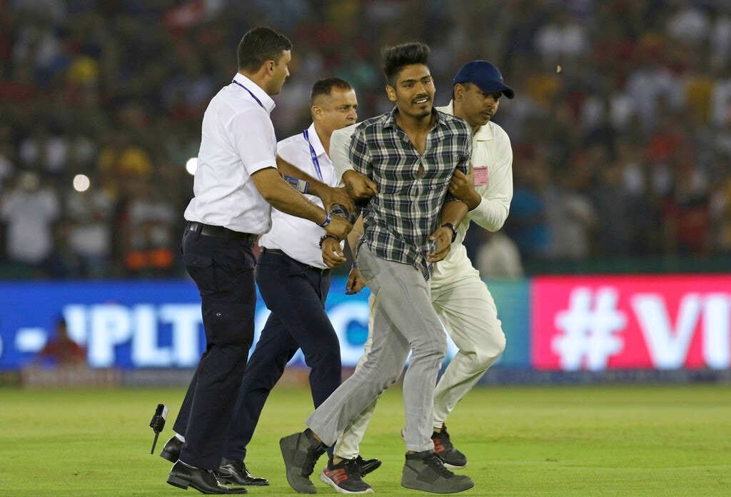 Security personnel catches a fan who entered the field to hug Virat Kohli, captain of Royal Challengers Bangalore, during the VIVO IPL T20 cricket match between Kings XI Punjab and Royal Challengers Bangalore in Mohali, India, Saturday, April 13, 2019. (AP Photo/Surjeet Yadav)
