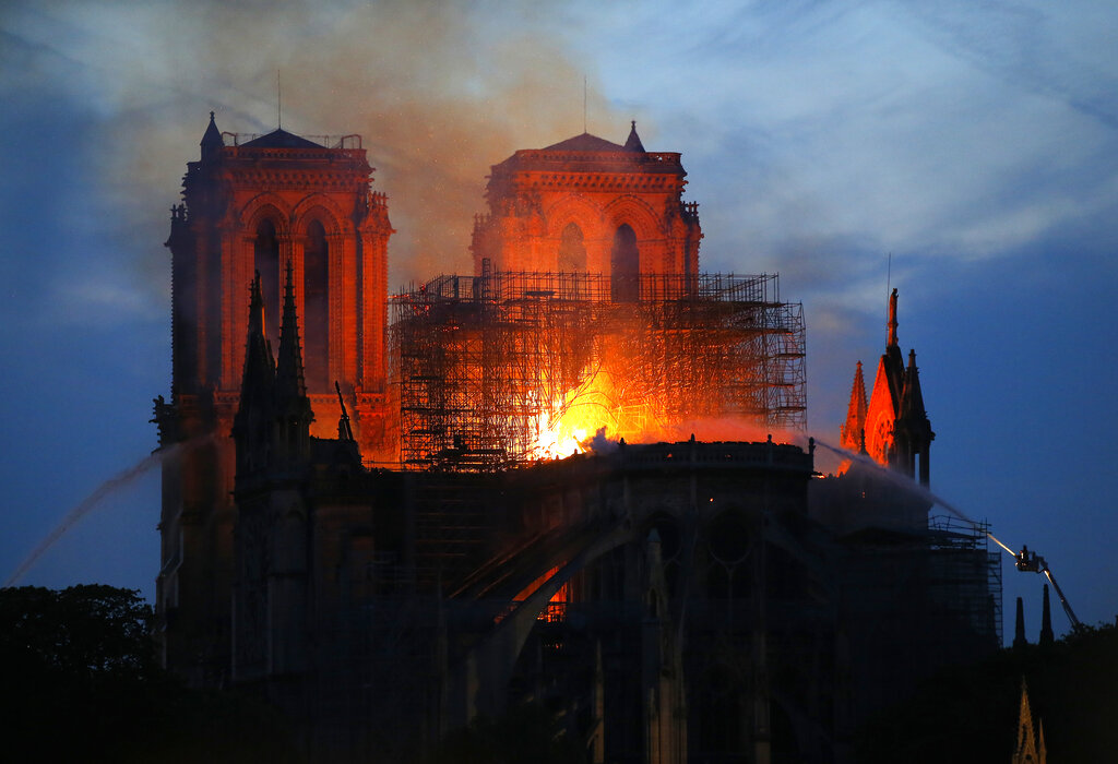 Firefighters tackle the blaze as flames and smoke rises from Notre Dame cathedral as it burns in Paris, Monday, April 15, 2019. (AP Photo/Michel Euler)
